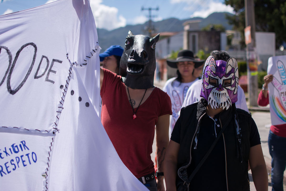 Two people wearing masks hold up a banner