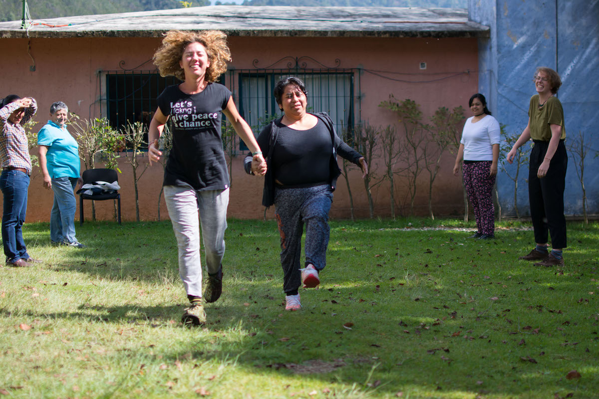 Two women run hand-in-hand with their eyes closed