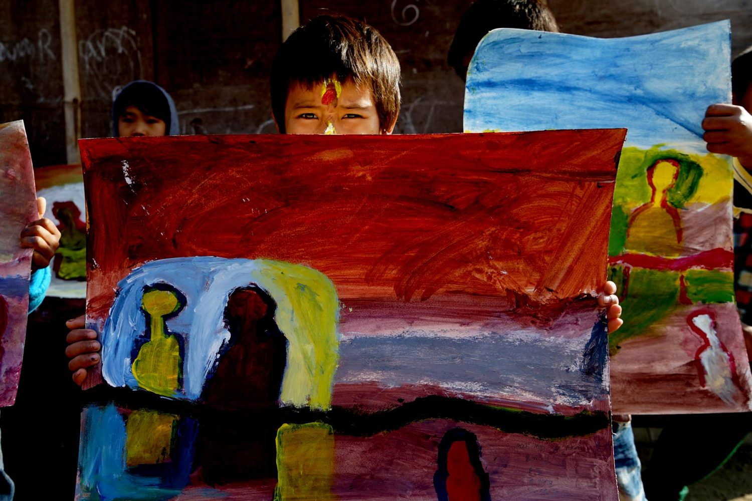 child holding up his finished painting