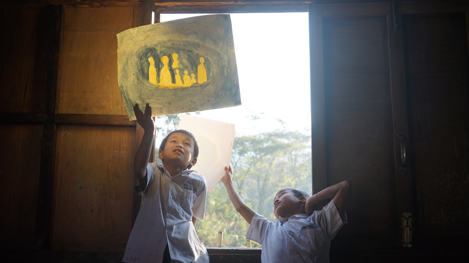 two children holding up their painting to the sky
