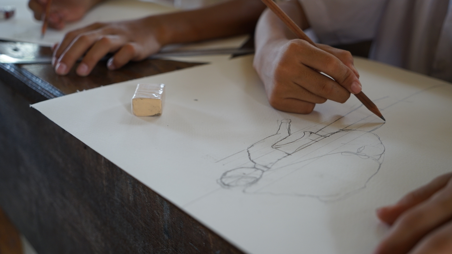 child sketching the human form in class