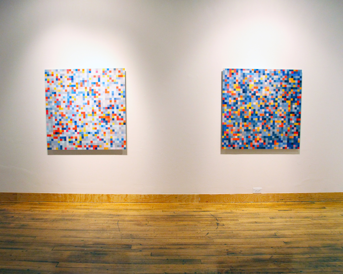 Two large square prints hang on a wall. Each contains many small squares of different colours and values in a seemingly random pattern.