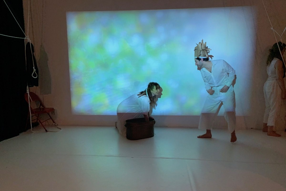 Two people in white outfits are on a stage with bluish light being projected on to them.