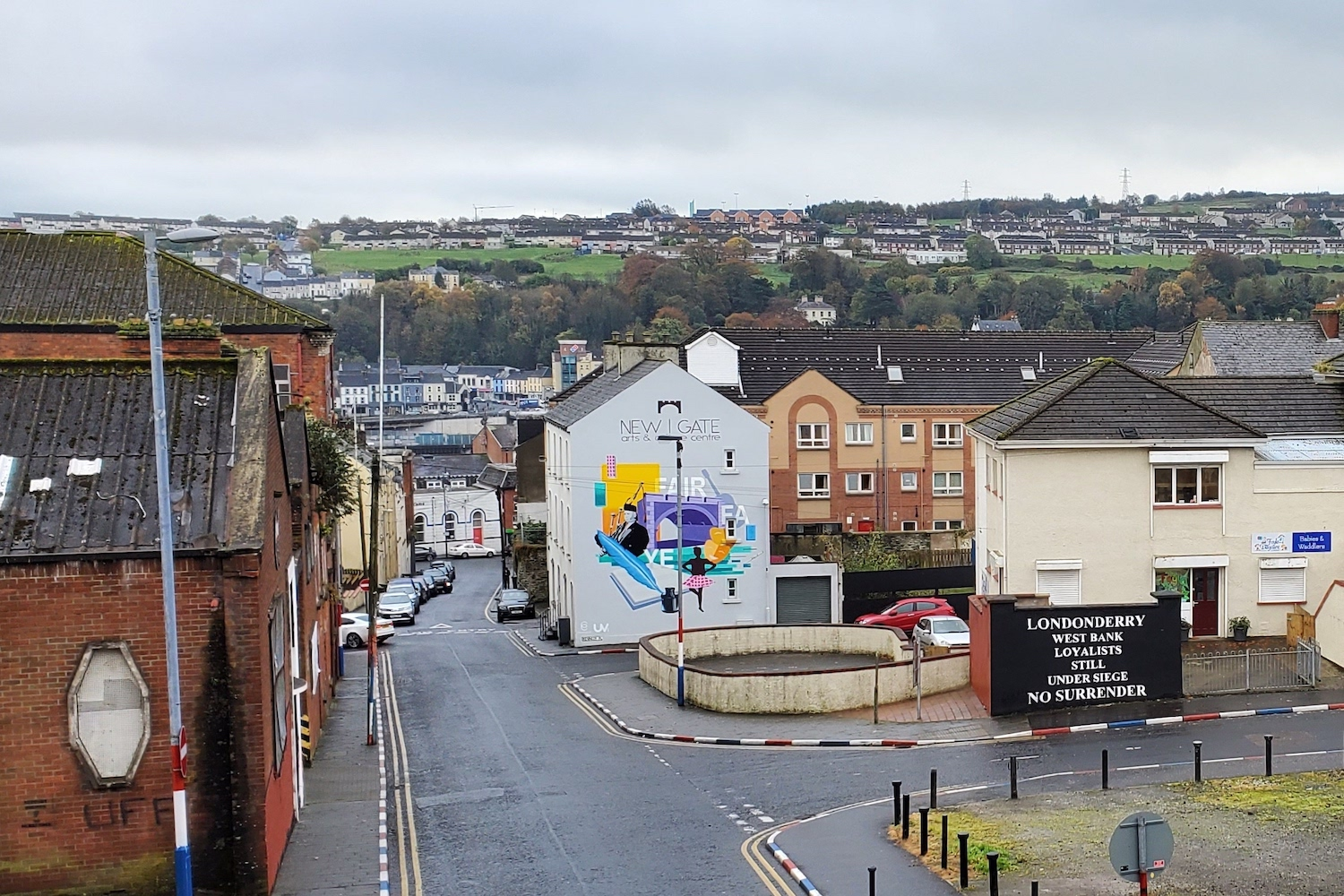 """Street intersection in Derry Ireland. A sign reads """"Londonderry West Bank Loyalists still under siege. No surrender."""""""