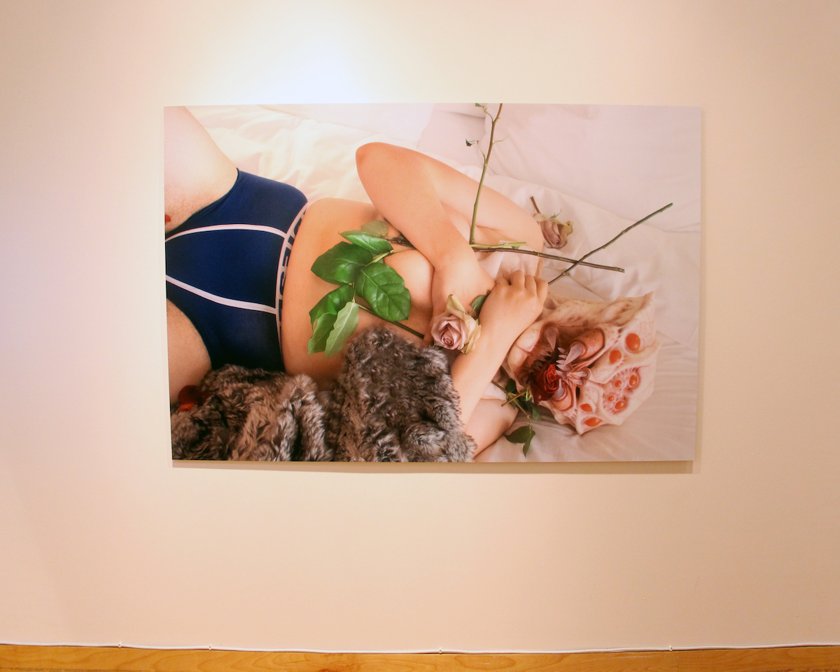 A large photographic print of a body covered in flowers with a spider head. An animal skin half obscures the body.