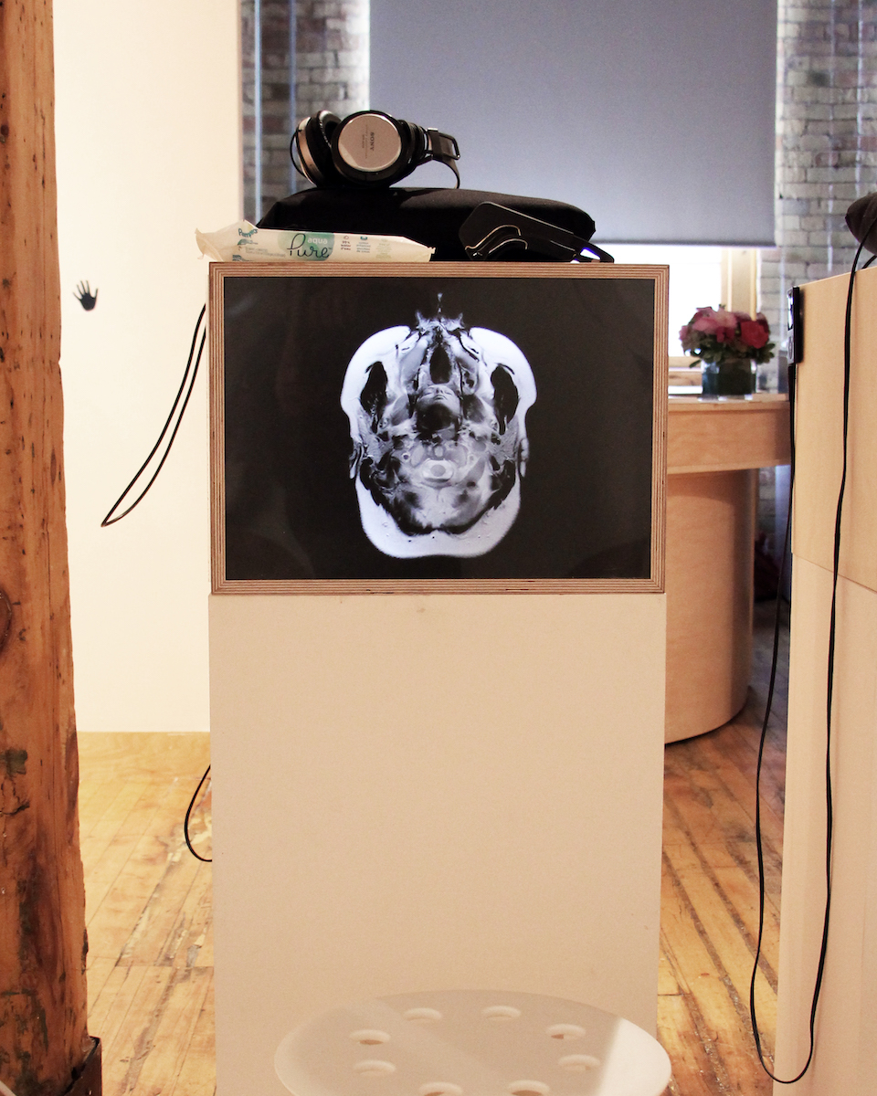 A photo of a rectangular column with a backlit photograph on it. A stool sits in front of the column, and a pair of headphones sit on top.
