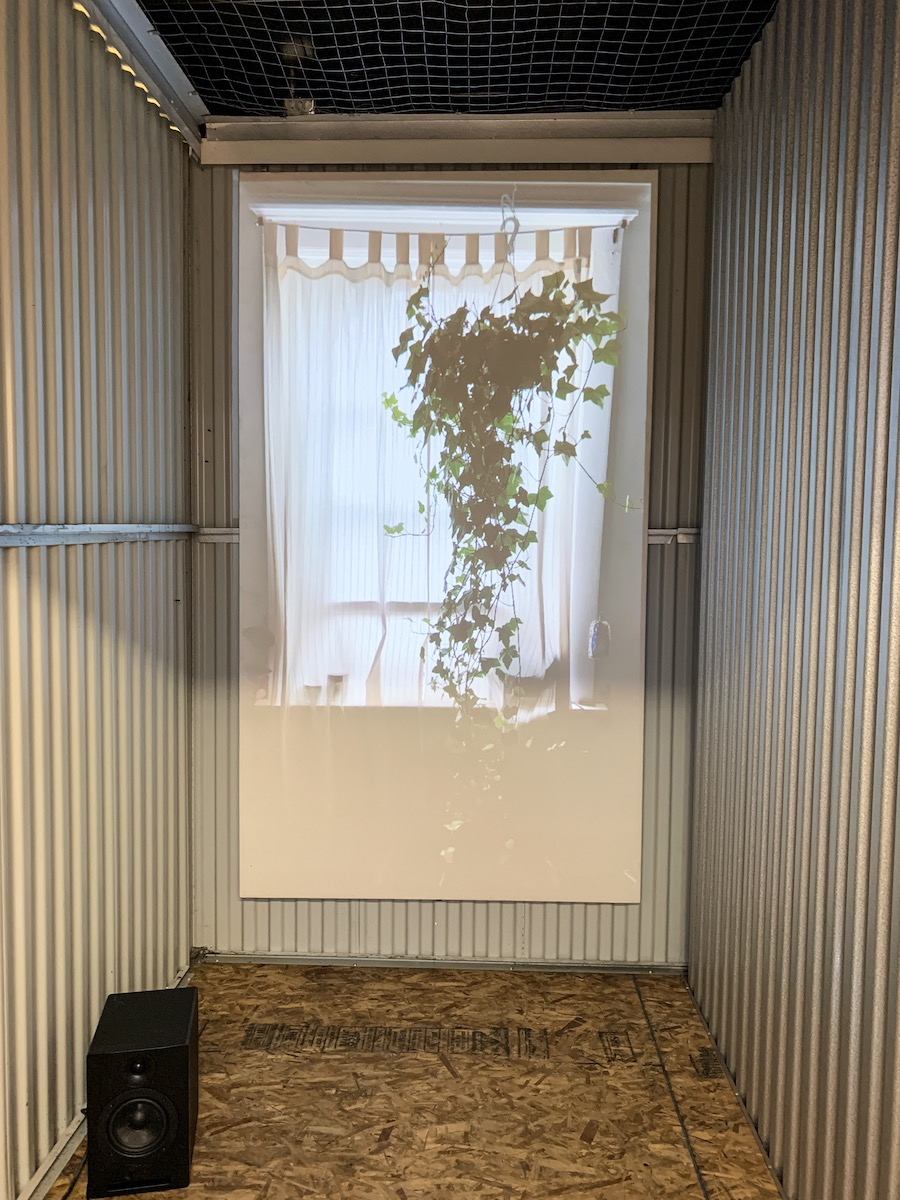 A photo of the interior of a corrugated metal room. On the back wall a photo of a curtained window and hanging plant is projected on to a white screen.