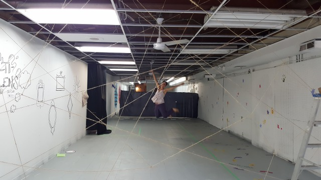 This is an image of a gallery space with a string installation and a person jumping into the air in the background
