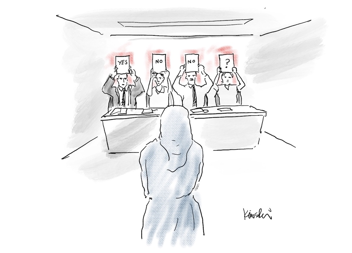 """A woman stands in front of a table. Four people sitting at the table hold up cards that read, """"Yes, No, No, question mark."""""""