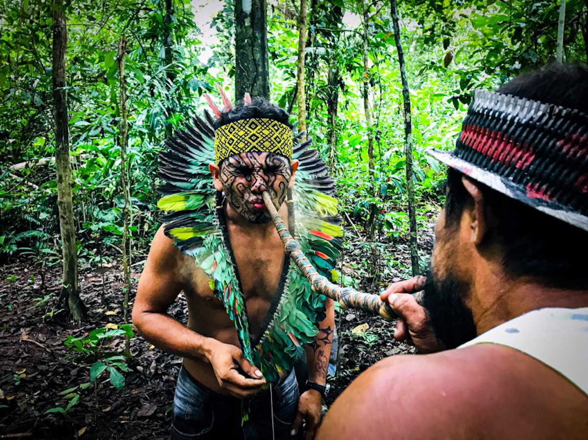 An Indigenous man dressed in traditional garb receives medicine through his nose via a long tube.