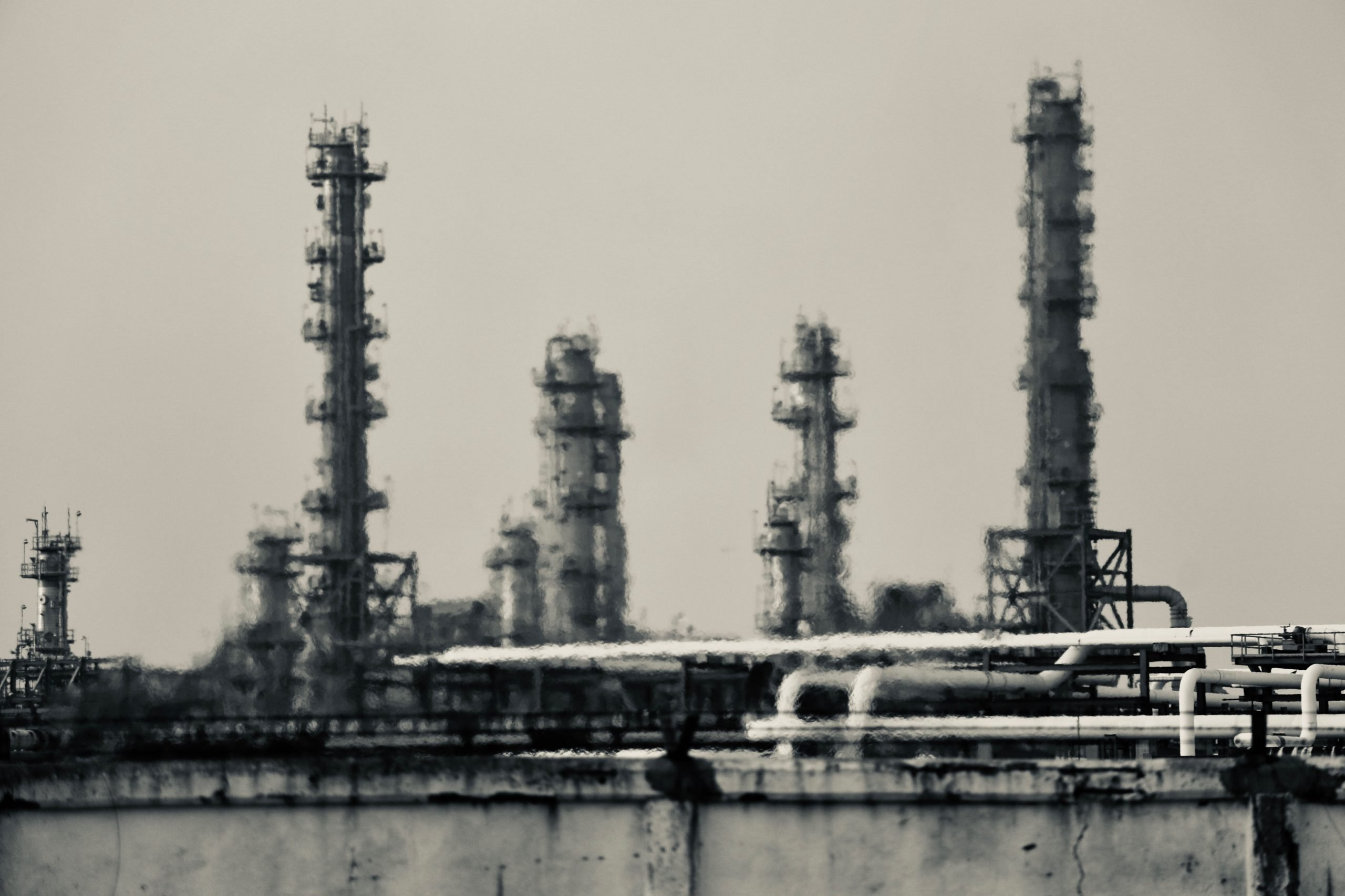 black and white image of oil refinery rippling in heat