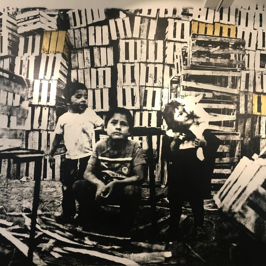 three children sitting surrounded by boxes