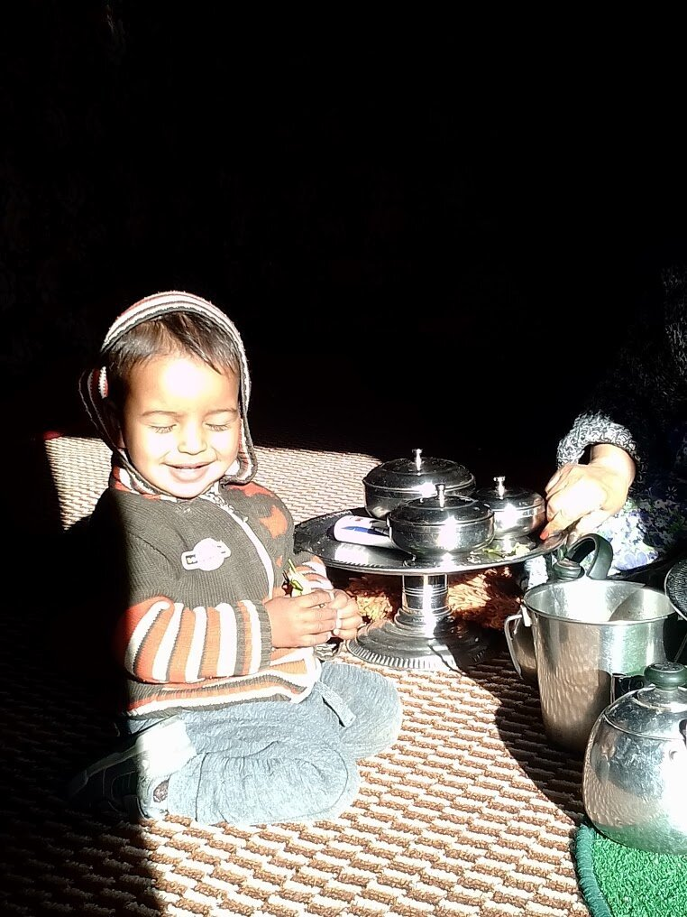 A toddler smiles in the sunlight while a woman's hand arranges a food tray.