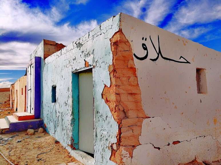Photo of a low rectangular building partially painted in vibrant colours under a blue sky. Cracked plaster at the corner of the building reveals worn bricks underneath.