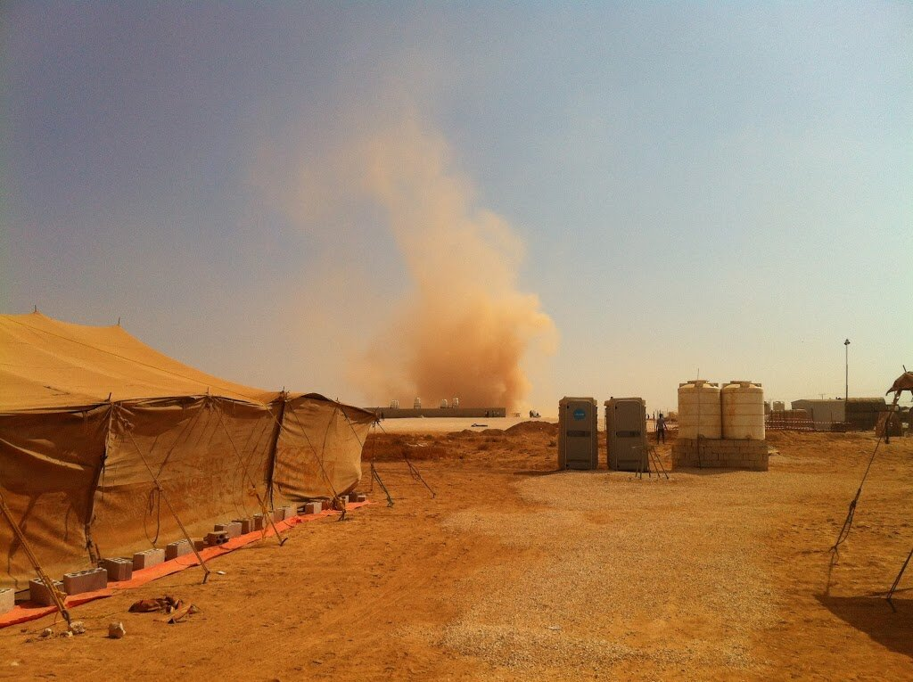 Photo of a large tent, water containers, and portable bathrooms, with a large swirl of dust rising in the background.